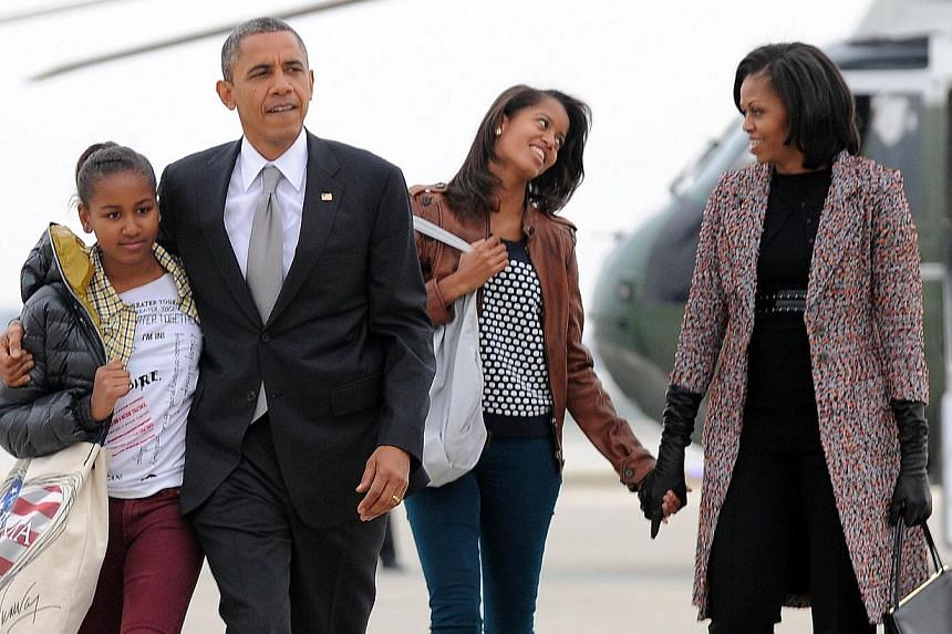 """In this November 7, 2012 file photo US President Barack Obama, First Lady Michelle Obama and their daughters Malia and Sasha(left) borad Air Force One at Chicago O'Hare International Airport in Chicago.US President Barack Obama says he is a """"go"""