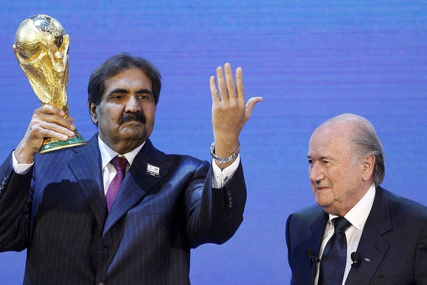 Qatar's Emir Sheikh Hamad bin Khalifa al Thani (left) holds up a copy of the World Cup he received from Fifa President Joseph S. Blatter (right) after the announcement that Qatar is going to be host nation for the Fifa World Cup 2022, in Zurich on De