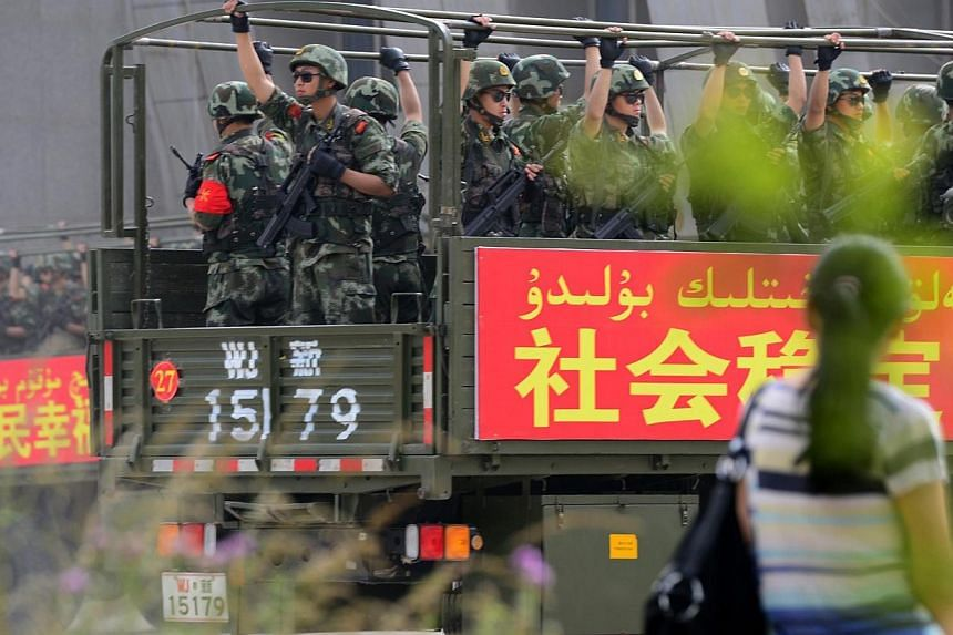 """This picture taken on June 6, 2014 shows security forces participating in a military drill in Hetian, northwest China's Xinjiang region.An extremist minority that rejects the Chinese Communist Party's """"care"""" is to blame for rising violence stem"""