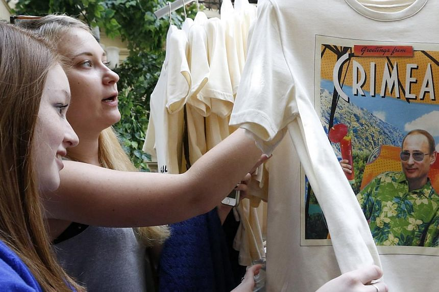 Women inspect T-shirts, displaying images of Russia's President Vladimir Putin, which are on sale at GUM department store in central Moscow, on June 11, 2014. -- PHOTO: REUTERS