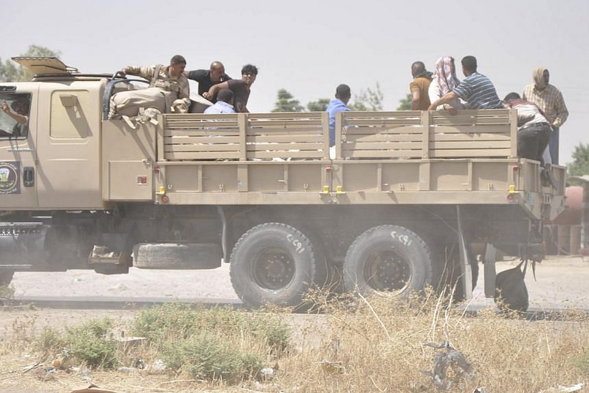 Iraqi security forces leave a military base as Kurdish forces take over control in Kirkuk on June 11, 2014. -- PHOTO: REUTERS
