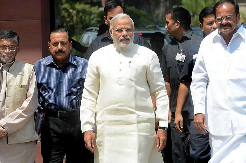 Indian Prime Minister Narendra Modi (centre) arriving with Minister of Parliamentary Affairs and Urban Development Venkaiah Naidu (right) for the first session of India's newly elected Parliament in New Delhi on June 4, 2014. -- FILE PHOTO: AFP