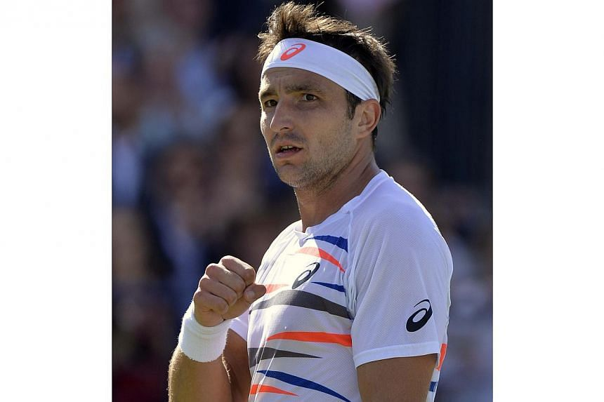 Australia's Marinko Matosevic celebrates defeating Croatia's Marin Cilic in their men's singles tennis match at the Queen's Club Championships tennis tournament in west London, on June 10, 2014. -- PHOTO: REUTERS