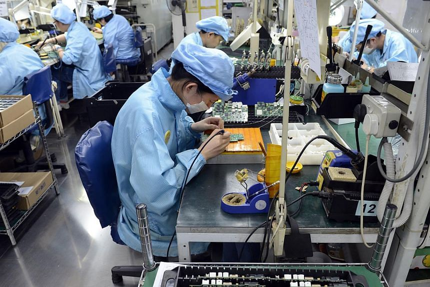 Workers at Add-Plus, an electronics manufacturing company that makes printed circuit boards. -- PHOTO: ST FILE