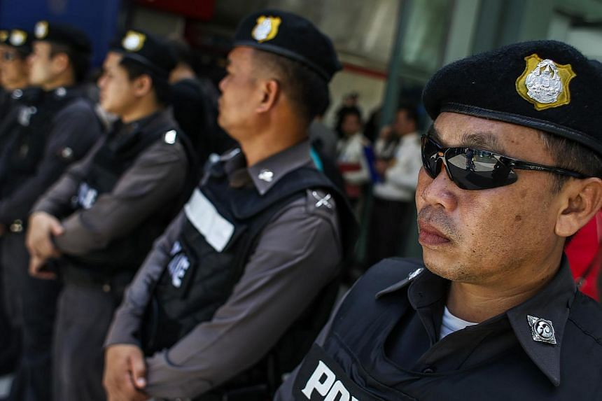 Police officers stand guard at a shopping mall in Bangkok on June 8, 2014. -- PHOTO: REUTERS