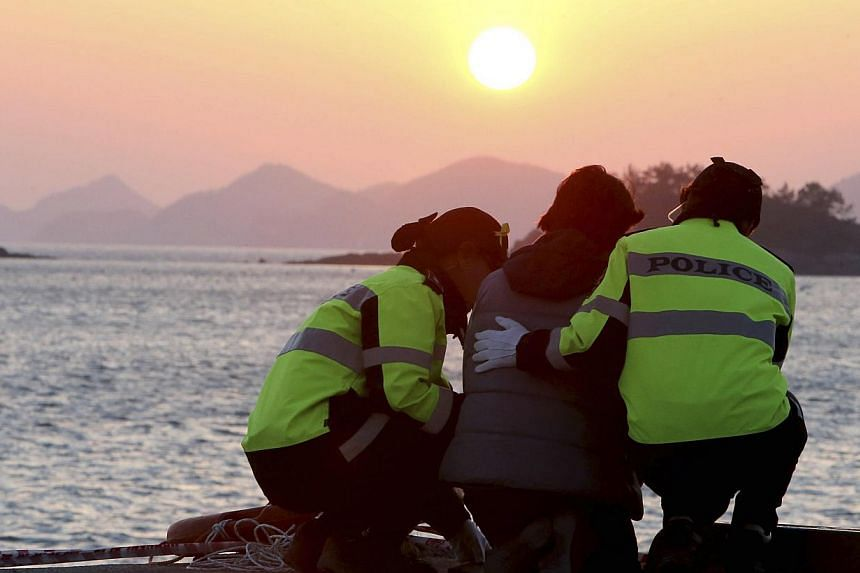 Policewomen comfort a family member (centre) of missing passengers onboard the capsized passenger ship Sewol, as she waits for news from a search and rescue operation team, during sunset at a port in Jindo on April 30, 2014. -- PHOTO: REUTERS
