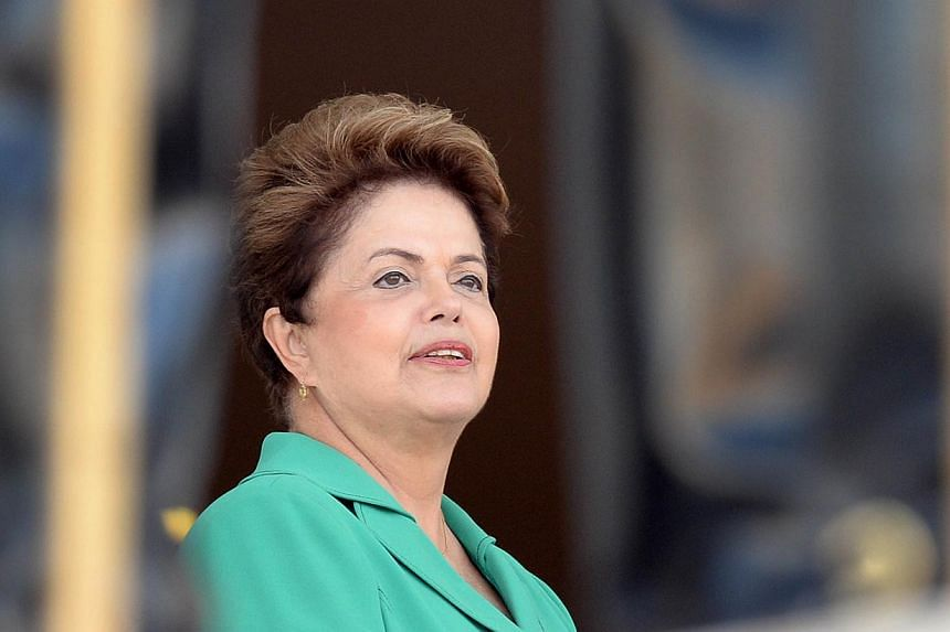 Brazil's President Dilma Rousseff waits the arrival of her Chilean counterpart Michelle Bachelet at the Planalto Palace in Brasilia on 12 June, 2014. -- PHOTO: AFP