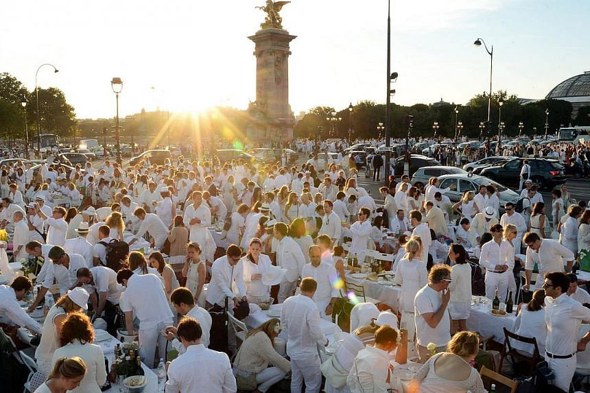 """Participants enjoy their meal during a """"Diner en Blanc"""" ('Dinner in White'), the world's only viral culinary event, a chic secret pop-up style picnic phenomenon originally started in France, on a bridge over the Seine river in Paris on June 12, 201"""