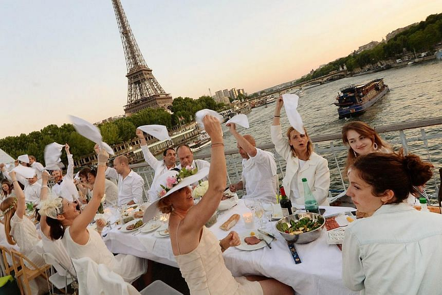 "Participants enjoy their meal during a ""Diner en Blanc"" ('Dinner in White'), the world's only viral culinary event, a chic secret pop-up style picnic phenomenon originally started in France, on a bridge over the Seine river in Paris on June 12, 201"