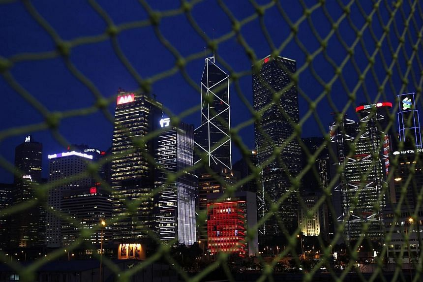 Skyscrapers at Hong Kong's central business district (from left),AIA Central, CCB Tower, Bank of China Tower, City Hall (in red), Cheung Kong Centre, HSBC headquarters and Standard Chartered Bank are seen behind a net near a construction site m