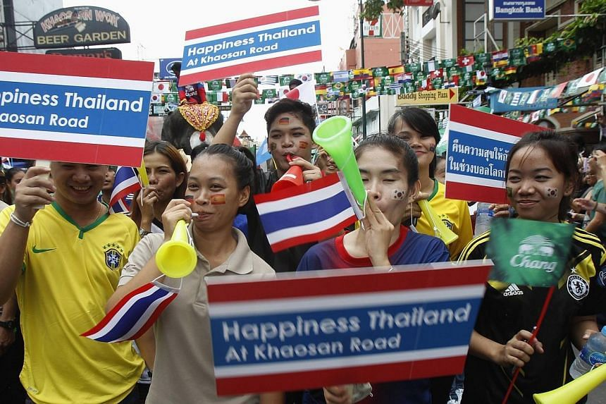 Workers hold placards during a celebration to boost tourism, along the Khaosan tourist street in Bangkok on June 13, 2014.Thailand's military government lifted a curfew nationwide on Friday, June 13, 2014, citing the absence of any violence and