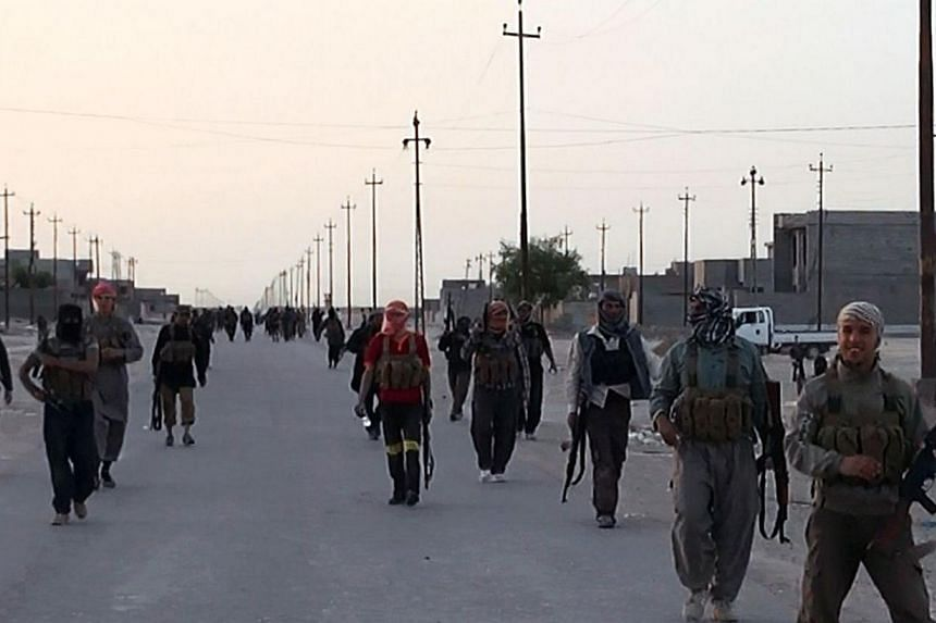 An image uploaded on June 9, 2014 on the jihadist website Welayat Salahuddin allegedly shows militants of the Islamic State of Iraq and the Levant (ISIL) taking position on a street in the northern Iraqi city of Samarra. Jihadists are pushing toward