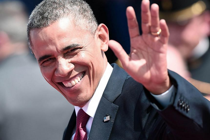 US President Barack Obama waves as he arrives to attend the international D-Day commemoration ceremony on the beach of Ouistreham, Normandy, on June 6, 2014. -- PHOTO: AFP