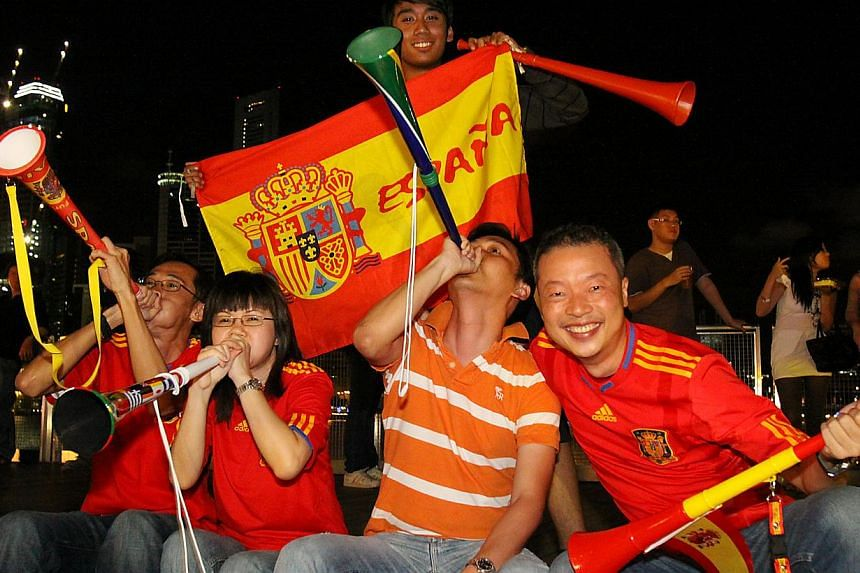 Soccer fans (from far left, seated) Vince Teo, Emily Koh, Tan Yu Ming, Alvin Soh and Nur Hisyam (standing) celebrate a Spain victory after watching a live match during the 2010 World Cup. -- PHOTO: THE NEW PAPER