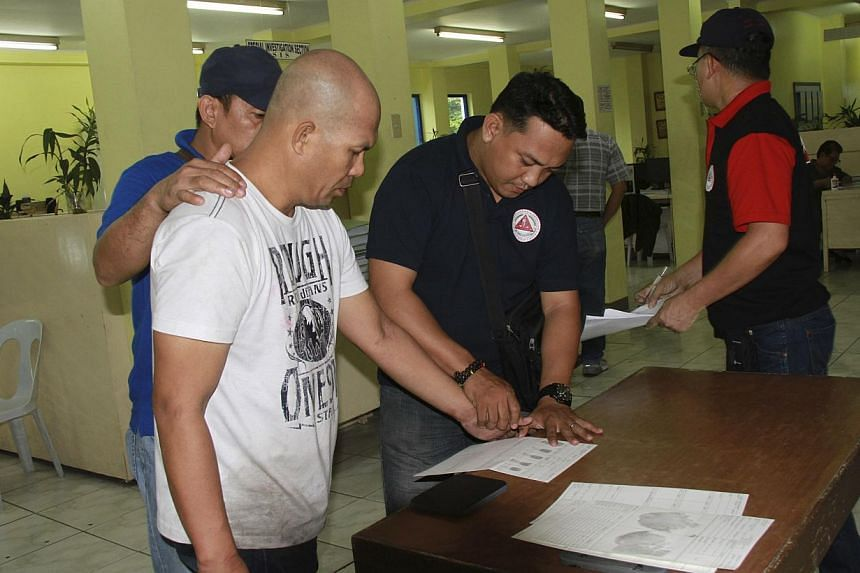 Philippine National Police handout picture shows a police investigator taking the fingerprint of militant Khair Mundos (left) inside a Philippine National Police (PNP) headquarters in Quezon city, metro Manila on June 11, 2014. -- PHOTO: REUTERS