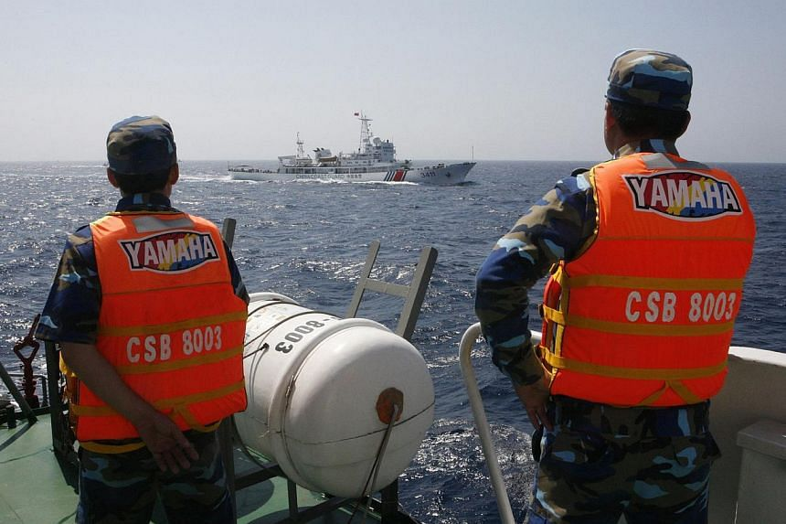 Officers of the Vietnamese Marine Guard monitoring a Chinese coast guard vessel (top) on the South China Sea, about 210km offshore of Vietnam in this May 15, 2014 file photo. A Chinese official said on Friday that China will never send military force