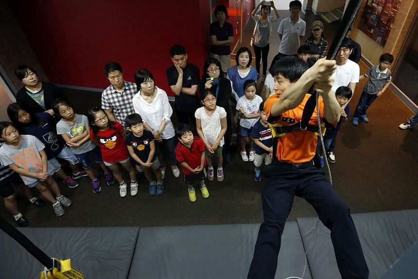 A fire officer demonstrating the use of the automatic descending lifeline to children during a fire safety course at a safety experience centre in Seoul on June 4, 2014. -- PHOTO: REUTERS