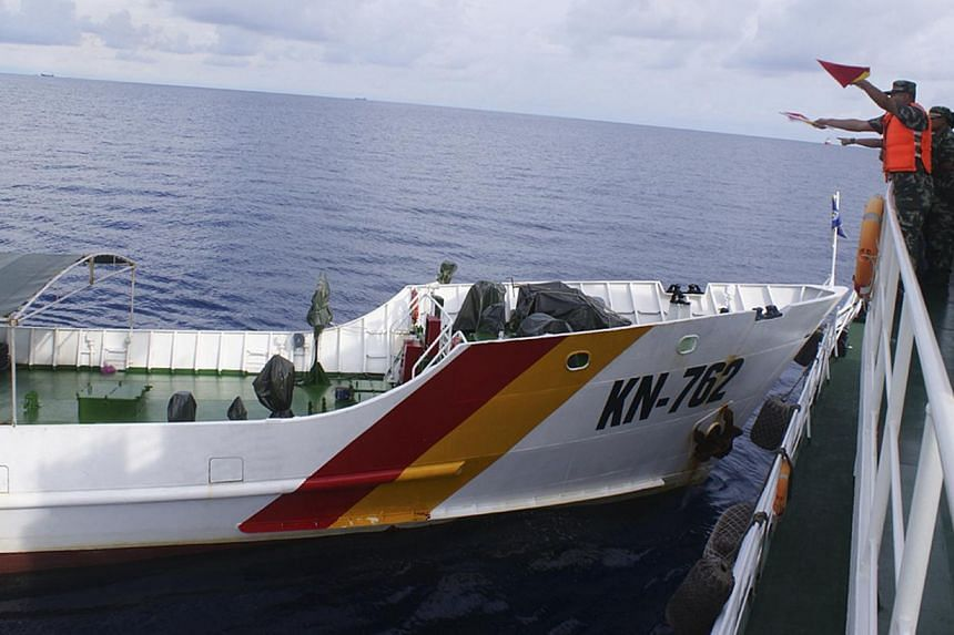 A Chinese maritime policeman (right) using flags to signal to Vietnamese ship KN-762 (left), which according to the Chinese authorities collided with Chinese coast guard ship 46001 in South China Sea, in this handout dated May 2, 2014 provided by the