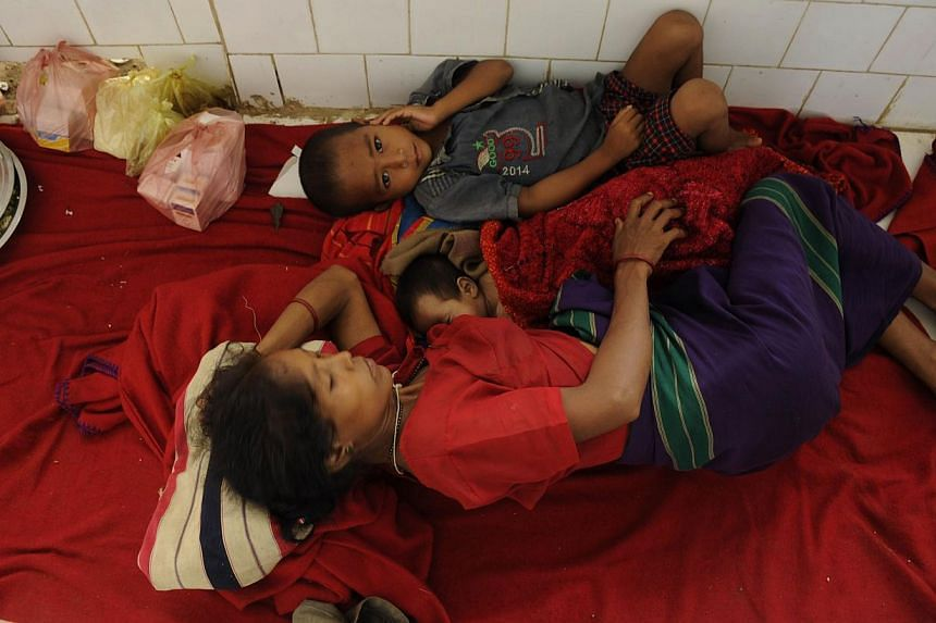 Indian residents infected with malaria lie on the floor of a primary health centre in Gandacharra, some 170 kms north of Agartala, the capital of north-eastern state of Tripura on June 13, 2014. At least 20 people have died from malaria in a rem