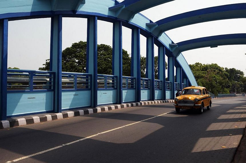 In this photograph taken on June 12, 2014, an Indian taxi drives along a bridge painted in shades of blue in Kolkata. -- PHOTO: AFP