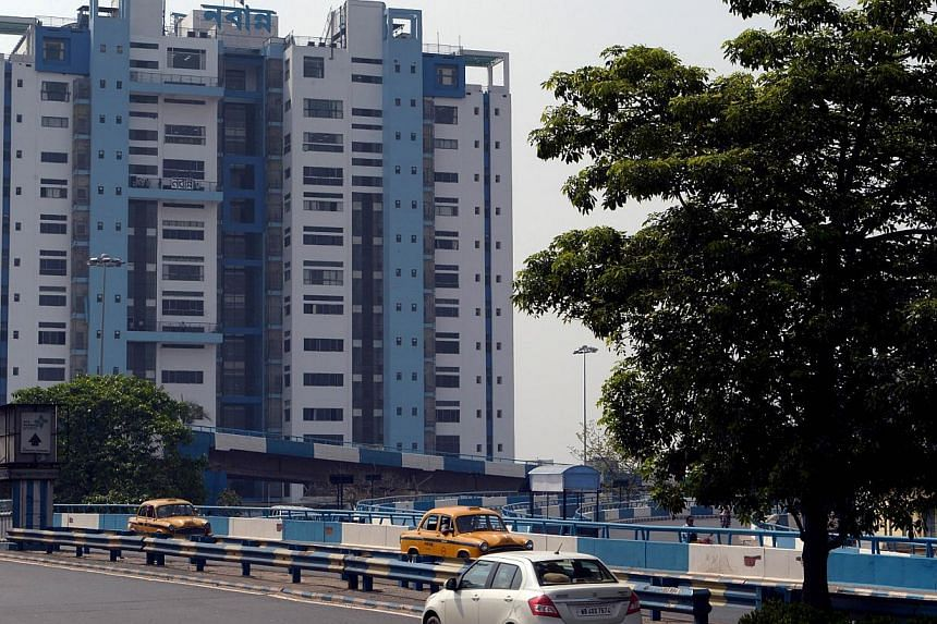 """In this photograph taken on June 12, 2014, cars drive past the state secretariat building called """"Nabanna"""", painted in shades of blue in Kolkata. -- PHOTO: AFP"""