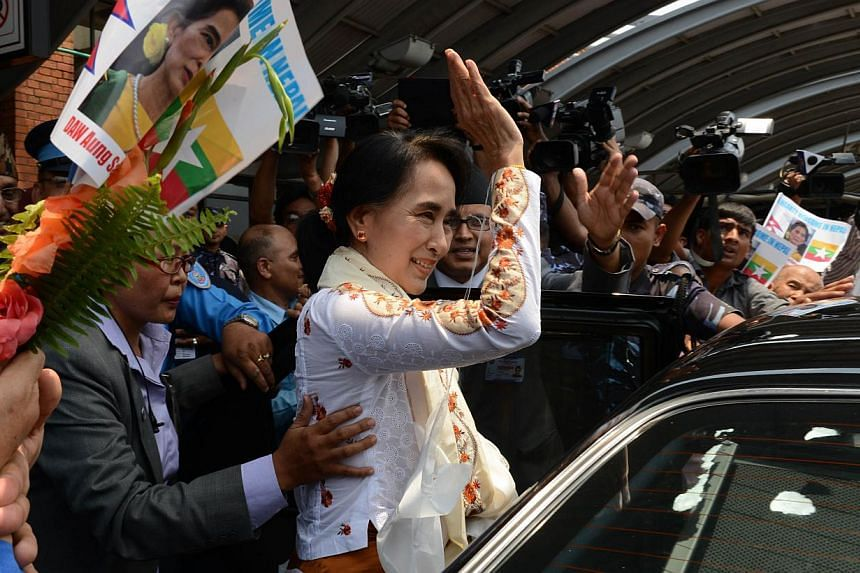 Myanmar's opposition leader and Nobel Peace Prize laureate Aung San Suu Kyi gestures on her arrival at Tribhuvan International airport in Kathmandu on June 13, 2014. Hundreds of supporters thronged Kathmandu's airport on Friday to welcome Myanma
