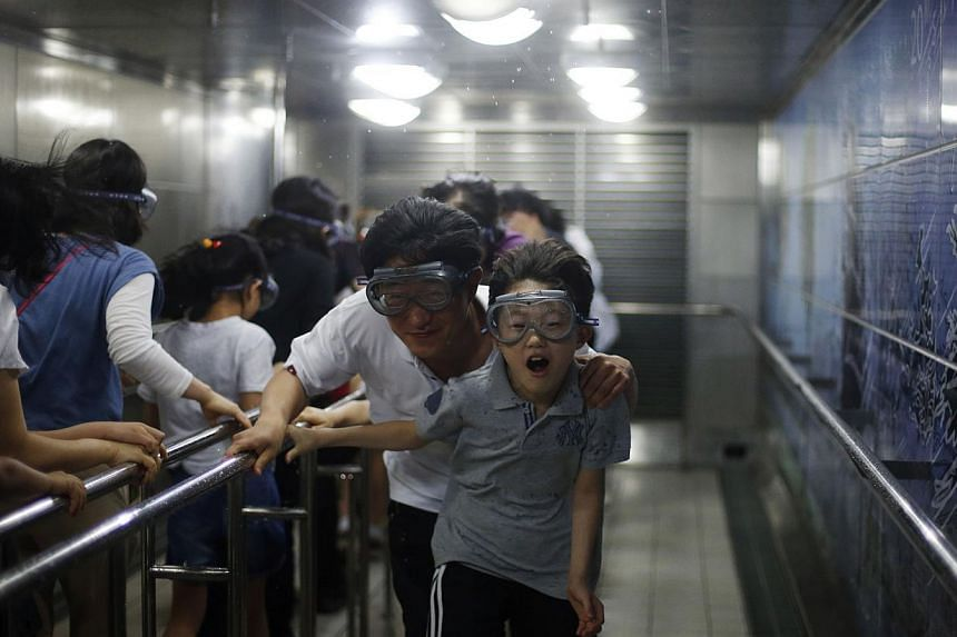 Children participate in a windstorm experience zone with their parents at a safety experience centre in Seoul on June 4, 2014. -- PHOTO: REUTERS
