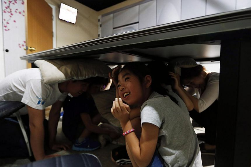 A girl participates in an earthquake experience zone with her parents at a safety experience centre in Seoul on June 4, 2014. -- PHOTO: REUTERS