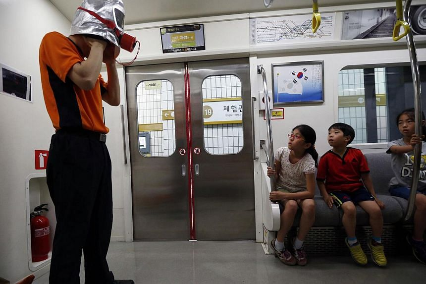 A fire officer demonstrates the use of a smoke mask to children at a subway accident experience zone at a safety experience centre in Seoul on June 4, 2014. -- PHOTO: REUTERS