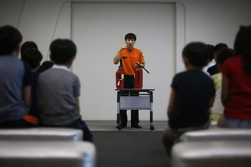 A fire officer demonstrates how to use a fire extinguisher to children during a fire safety course at a safety experience centre in Seoul on June 4, 2014. -- PHOTO: REUTERS
