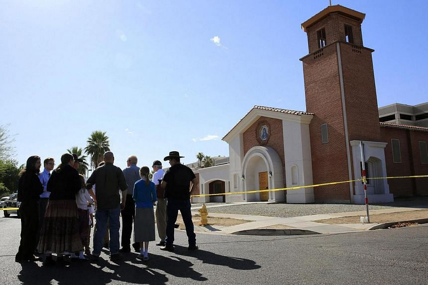 Parishioners arrive to pray, outside the Mater Misericordiae (Mother of Mercy) Mission Catholic church in Phoenix, Arizona on June 12, 2014.Police were hunting for a gunman or gunmen who killed one priest and injured another at a Catholic churc