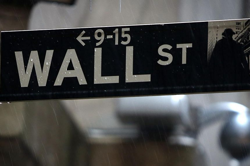 A Wall Street sign is pictured in the rain outside the New York Stock Exchange in New York on June 9, 2014. -- PHOTO: REUTERS