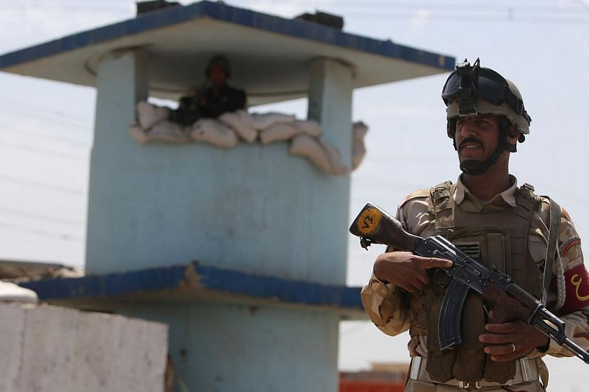 An Iraqi soldier stands guard at a checkpoint in the Iraqi town of Taji, at the entrance of Baghdad, on June 13, 2014, as security forces are bolstering defenses in the capital. -- PHOTO: AFP