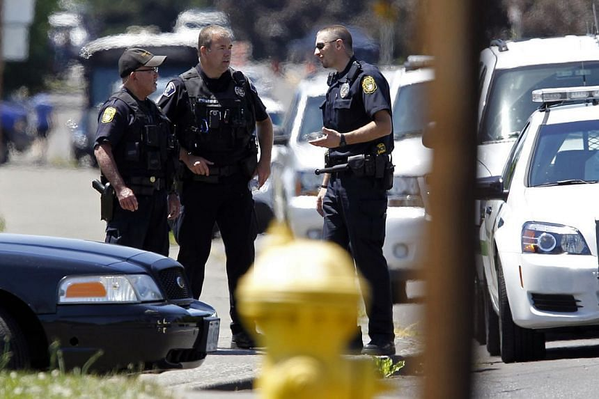 Police officers stand on the sidewalk after a shooting at Reynolds High School in Troutdale, Oregon on June 10, 2014. -- PHOTO: REUTERS