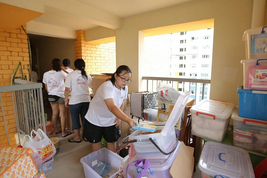 Cass Eng, 13, who benefited from a previous HSBC corporate responsibility event, lending a hand in this year's effort. Here she is sorting out a household's belongings while their flat is being cleared to make way for new furniture.