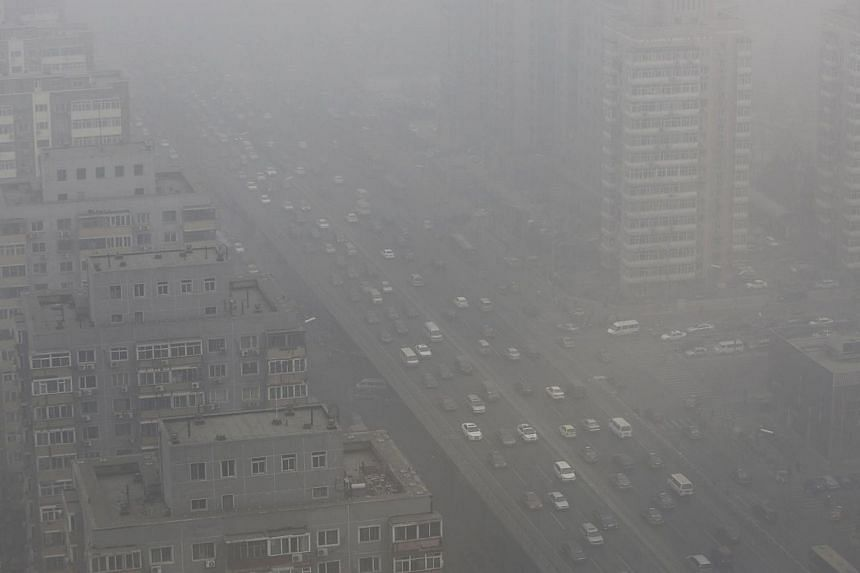 Cars drive on the Three Ring Road amid heavy haze in Beijing in this Feb 26, 2014, file photo. -- PHOTO: REUTERS