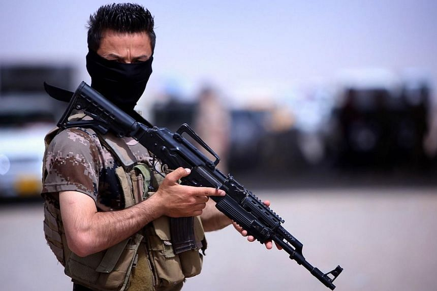 A masked Pershmerga fighter from Iraq's autonomous Kurdish region guards a temporary camp set up to shelter Iraqis fleeing violence in the northern Nineveh province, in Aski kalak, 40km west of the region's capital Arbil, on June 13, 2014. -- PHOTO: