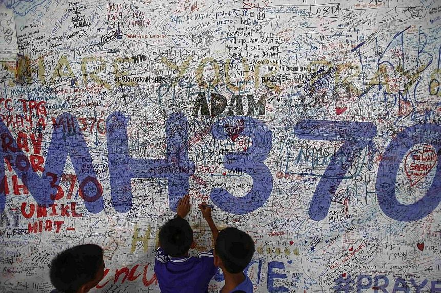 Children write messages of hope for passengers of missing Malaysia Airlines Flight MH370 at Kuala Lumpur International Airport (KLIA) outside Kuala Lumpur June 14, 2014.A commercial pilot has co-written a book on missing Malaysian Airlines Flig