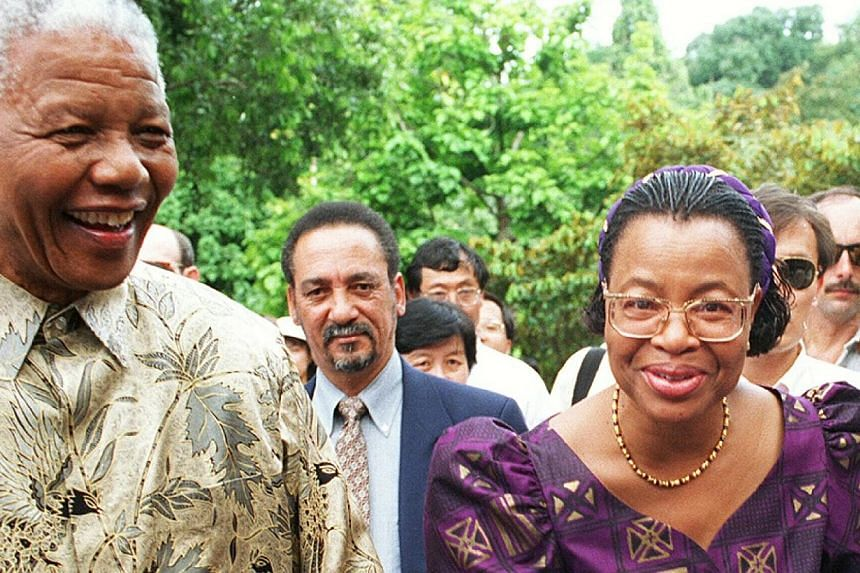 Mr Nelson Mandela's widow Graca Machal (right, pictured with Mr Mandela) was treated badly by members of his family as the peace icon was fighting for his life in hospital, excerpts from a memoir by his long-time aide have revealed. -- ST FILE PHOTO