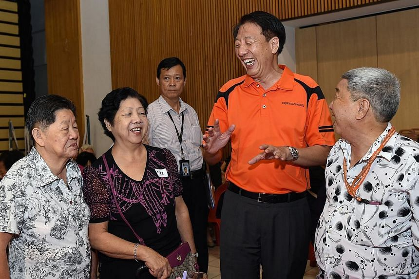 DPM Teo Chee Hean explains the details of the Pioneer Generation Package to Pasir Ris residents (from left) Mdm Choo Pin, 80, Mdm Ang Ah Moy, 72, and her husband (right) Mr Ng Nam Huat, 77. Those who qualify for Pioneer Generation Package benefi