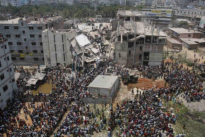 Crowds gather at the collapsed Rana Plaza building as people rescue garment workers trapped in the rubble, in Savar, 30km outside Dhaka in this April 24, 2013 file photo.Bangladesh's Anti-Corruption Commission (ACC) on Sunday filed a case with