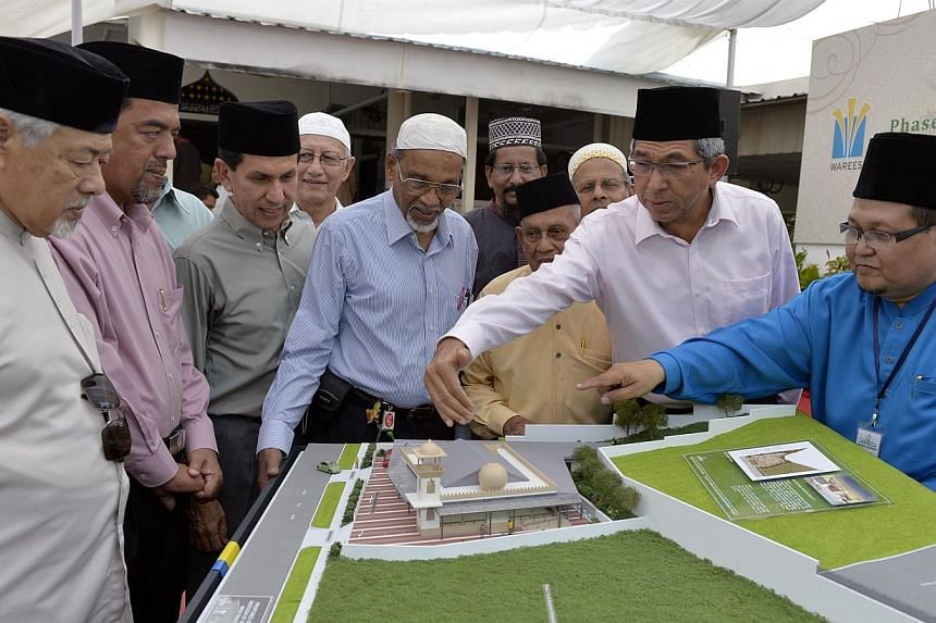 Minister for Communications and Information and Minister-in-charge of Muslim Affairs, Dr Yaacob Ibrahim (second from right) and guests looking at a model of the new proposed upgrade of the Al Huda Mosque .Universal health insurance plan Medishi