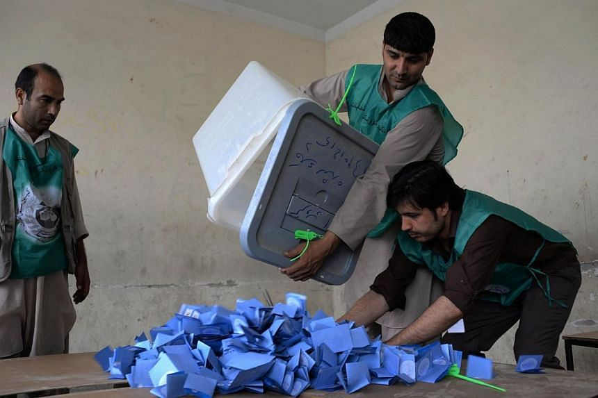 Afghan election workers empty a ballot box during the counting process at a polling station in Mazar-i-Sharif on June 14, 2014. A roadside bomb killed 11 people including five election workers in northern Afghanistan, officials said Sunday, June