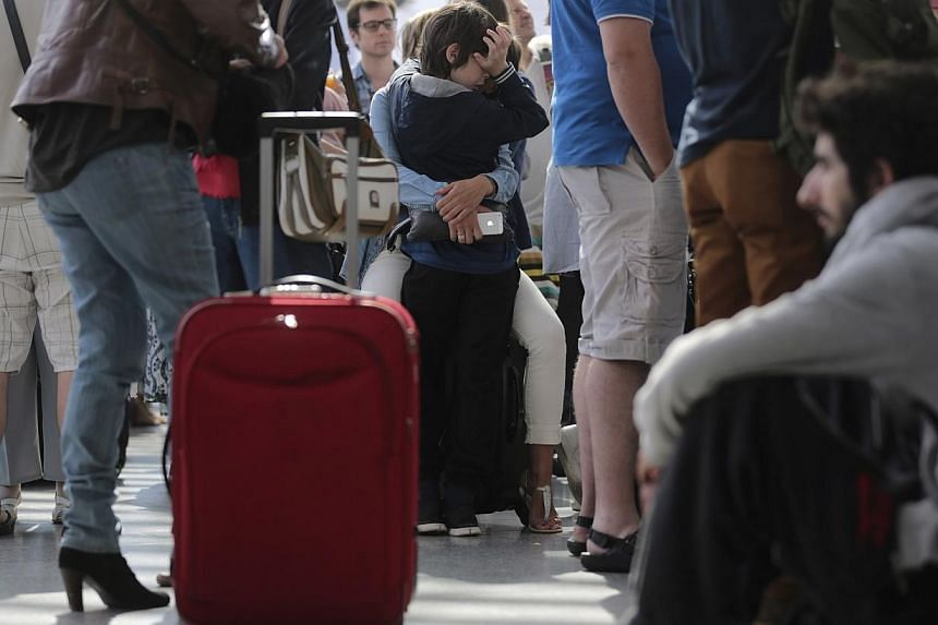 Passengers wait for their trains during a strike by French SNCF railway workers at Paris Gare de Lyon station on June 15, 2014.A crippling French railway strike has been extended into a sixth day on Monday, forcing the authorities to implement