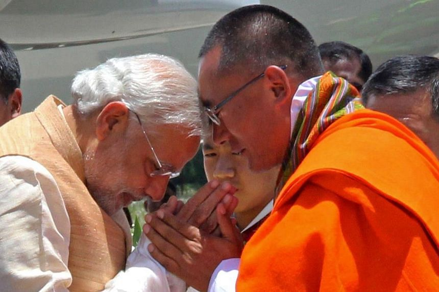 Indian Prime Minister Narendra Modi (left) gestures as he is met by Bhutanese Prime Minister Tshering Tobgay (right) at Paro Airport on June 15, 2014.  India's Prime Minister Narendra Modi received a grand welcome to Bhutan on Sunday, June