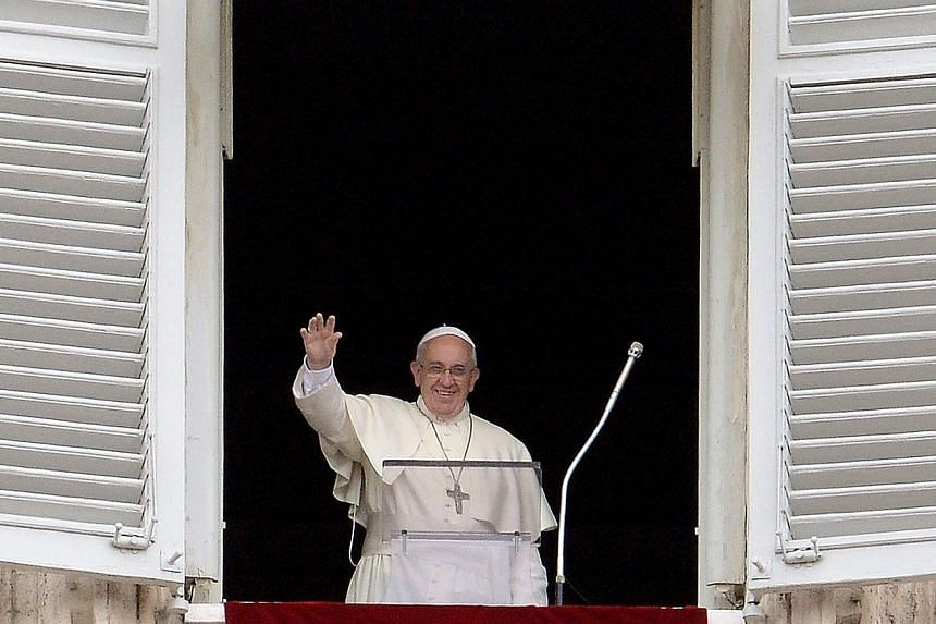 Pope Francis waves from the window of his study overlooking St.Peter's Square at the Vatican as he leads the Sunday Angelus prayer on June 15, 2014.Pope Francis said on Sunday, June 15, 2014, his first trip to a European country would be to Alb