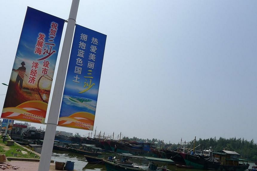 """Posters adorn lamp posts in Tanmen fishing village, urging locals to """"love Sansha city, embrace China's blue-water territory"""".China has begun building a school on Sansha, part of the contested Paracel islands, state media reported, as the Asian"""