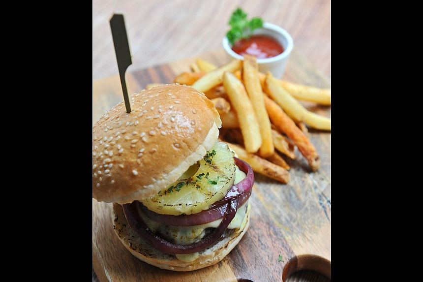 The breezy non-airconditioned cafe serves hearty sandwiches, burgers (above), pastas, pizzas and fish and chips. -- ST PHOTO: MATTHIAS HO