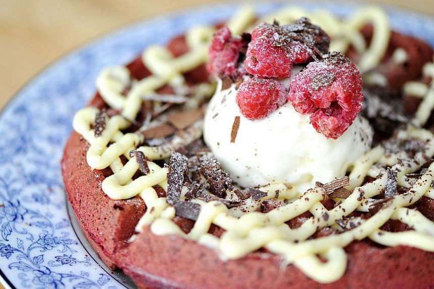 Dishes to be found at Bali Lane include red velvet waffles (above) at Stateland Cafe, pita bread at Pita Bakery and crispy fried chicken at Korean restaurant Choo Choo Chicken, co-owned by Ms Lee Soon Young, 33. -- PHOTO: ST FILE