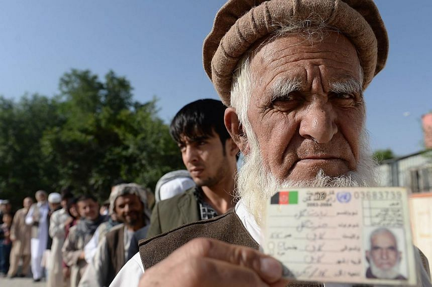 An Afghan resident wanting to vote poses for a photograph with his identity card as he waits for voting to start at a polling centre in Kabul on June 14, 2014.The White House welcomed Afghanistan's presidential run-off election on Saturday as